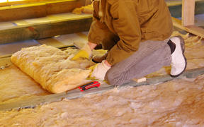 13534764 - construction worker thermally insulating house attic with glass wool