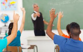 20235288 - group of students with hands up in classroom during a lesson