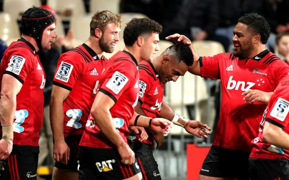The Crusaders celebrate one of Sevu Reece's two tries in the win over the Hurricanes.