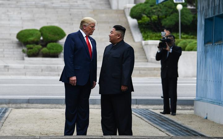 North Korea's leader Kim Jong Un talks with US President Donald Trump as they stand north of the Military Demarcation Line that divides North and South Korea, in the Joint Security Area (JSA) of Panmunjom in the Demilitarized zone (DMZ) on June 30, 2019.