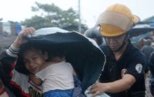 A fireman helps a mother and her family evacuate from their house in Manilla.