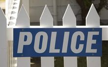 Police sign on fence.