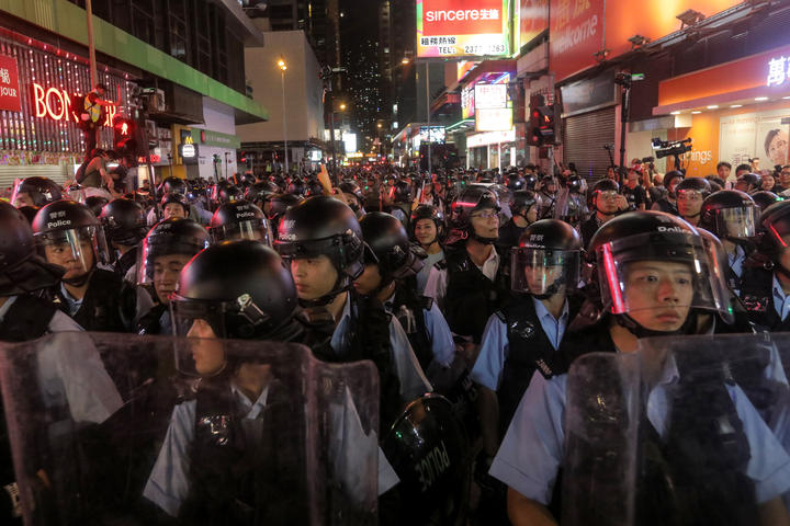 Police gather as they face protesters in the Mong Kok district in Kowloon after taking part in a march to the West Kowloon rail terminus against the proposed extradition bill in Hong Kong on July 7, 2019.