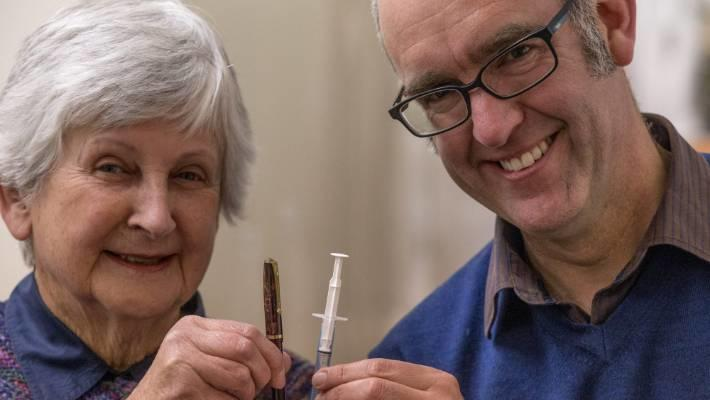 Marilyn Murdoch and Chris Rapley from South Canterbury Museum hold Colin Murdoch's fountain pen and prototype disposable plastic syringe.