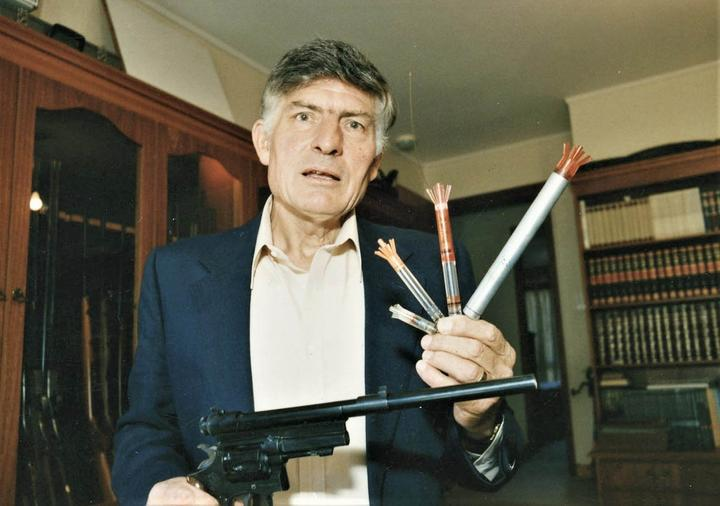 Colin Murdoch holds a tranquiliser gun and darts of his own invention.