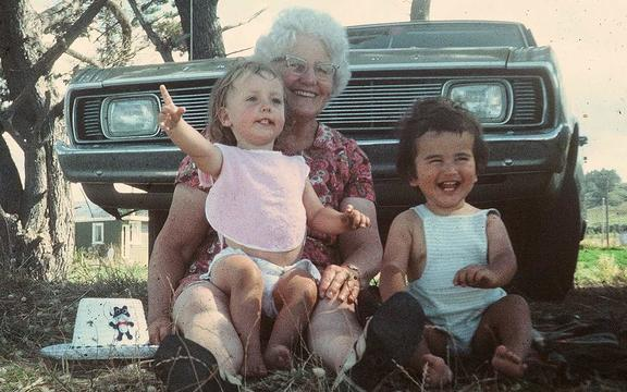 Two babies on knee of an older woman on the grass in front of a 70s car.
