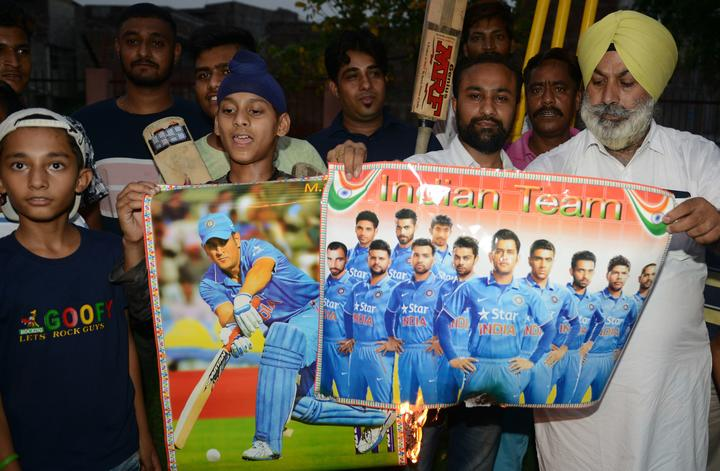 Indian cricket fans burn posters of Indian cricket players during a protest in reaction to the  national cricket team poor performance during the first semifinal between India and New Zealand at Old Trafford in Manchester of the 2019 ICC World Cup, in Amritsar June 10, 2019.