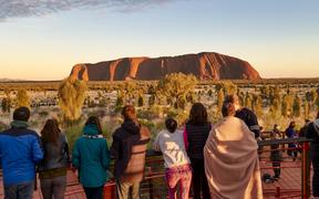 People enjoying the first sunlight of sunrise at Uluru (Ayers Rock), the sacred sandstone rock formation, Uluru-Kata Tjuta National Park, UNESCO World Heritage Site, Northern Territory, Australia,