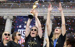 USA women's soccer player Megan Rapinoe (C) and other team members celebrate with the trophy in front of the City Hall after the ticker tape parade for the women's World Cup champions on July 10, 2019 in New York.