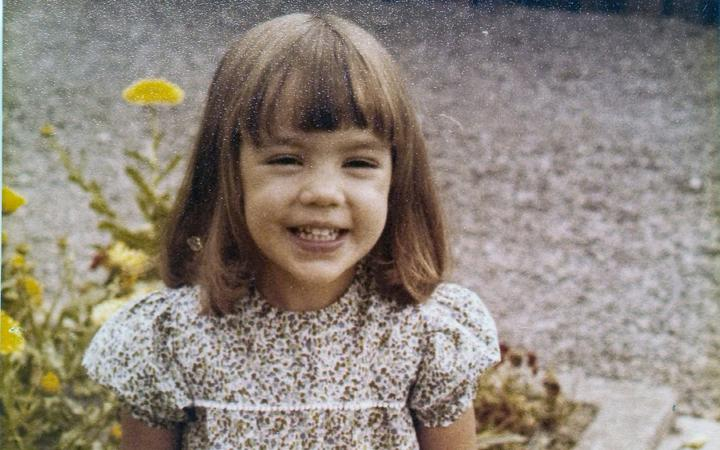 70's photo of young girl with a bob in a floral dress
