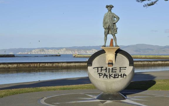 """Graffiti on the statue of James Cook reading """"Thief Pakeha""""."""