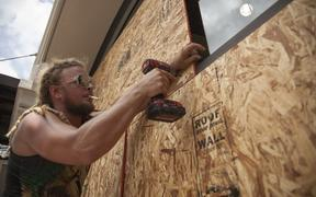 Matt Harrington boards up a Vans shoe store near the French Quarter in New Orleans as tropical storm Barry approaches.