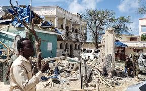 A man passes in front of the rubbles of the popular Medina hotel of Kismayo on July 13, 2019, a day after at least 26 people, including several foreigners, were killed and 56 injured in a suicide bomb and gun attack claimed by Al-Shabaab militants.