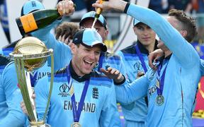 England's captain Eoin Morgan is covered in champagne as he poses with the World Cup trophy as England's players celebrate their win after the 2019 Cricket World Cup final between England and New Zealand at Lord's Cricket Ground in London on July 14, 2019.