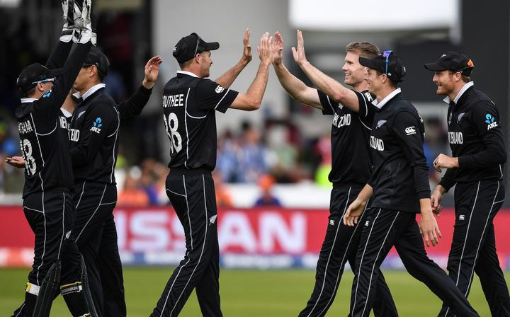 NZ players celebrate the wicket of Morgan.
