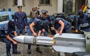 Italian policemen carry an air-to-air missile, as part of a big cache of guns and ammunition that was seized by the Turin special police force
