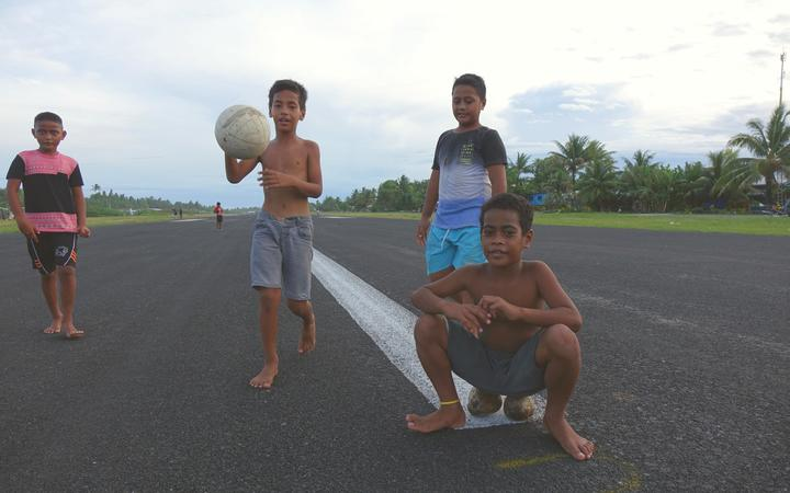 Boys play on the runway, whih takes up most of the space on narrow Fogafale, Tuvalu