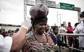 A woman gets her temperature measured at an Ebola screening station as she enters Rwanda from the  Democratic Republic of the Congo, 16 July 2019