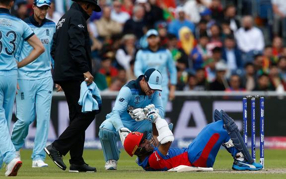 Hashmatullah Shahidi of Afghanistan  receives attention after being hit on the helmet England bowler by Mark Wood during a World Cup match in Manchester.