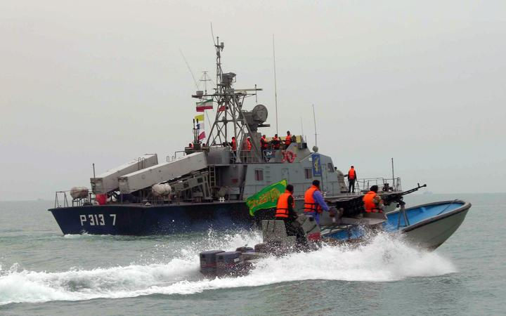 A picture released by the official Iranian News Agency shows members of Iran's elite Revolutionary Guard riding their boat along with an Iranian naval vessel during manoeuvers along the Gulf Sea and Sea of Oman, 03 April 2006.