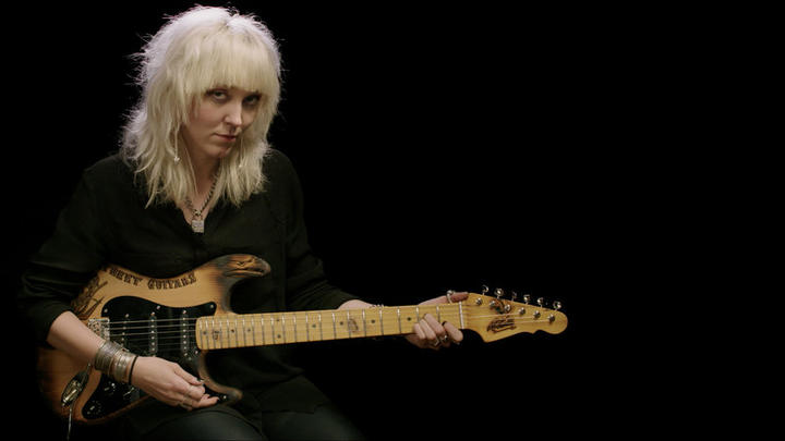 Cindy Hulej of Carmine Street Guitars holding a stratocaster style guitar