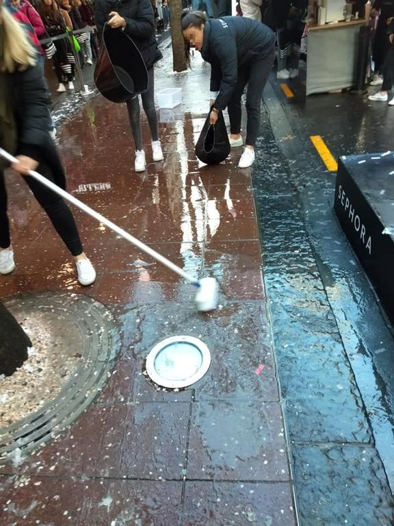 Sephora staff sweep debris into the drains in Auckland.