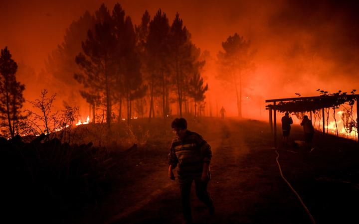 A villager walks past a wildfire encroaching on her home in Amendoa in Macao, central Portugal on 21 July, 2019.