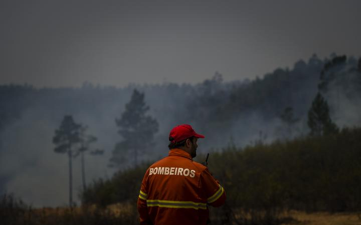 A firefighter monitors a wildfire in Sarnadas, Macao, in central Portugal, on July 21, 2019.