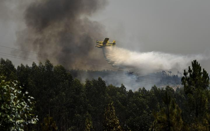 A firefighter plane drops water over a wildfire in Amendoa, Macao, in central Portugal on July 21, 2019.