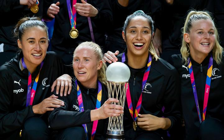 New Zealand captain Laura Langman holds the Netball World Cup trophy  with Maria Folau, Phoenix Karaka and Shannon Saunders after victory over Australia.