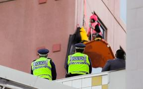 Police keep an eye as Greenpeace activists climb Wellington's Majestic Centre, the city's tallest building.