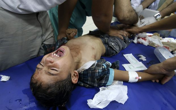 Medics tend to a boy injured in the shelling of a Gaza hospital.