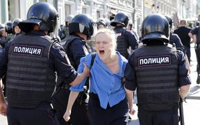 Police officers detain a protester during an unauthorised rally in downtown Moscow on July 27, 2019.