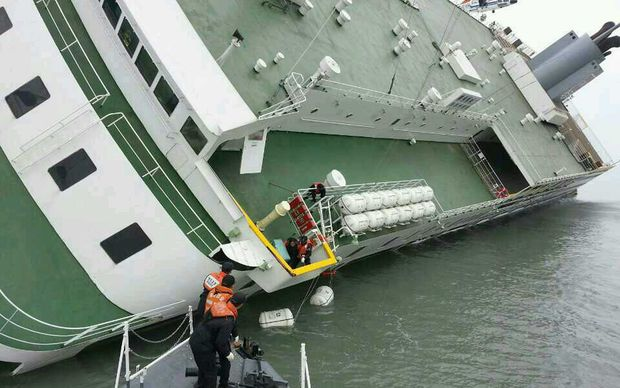 Passengers are helped to safety from the badly listing ferry.