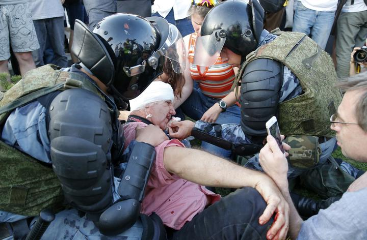 Servicemen of the Russian National Guard help an injured man during an unauthorised rally