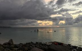 Funafuti lagoon, Tuvalu at sunset with a few  people in the water