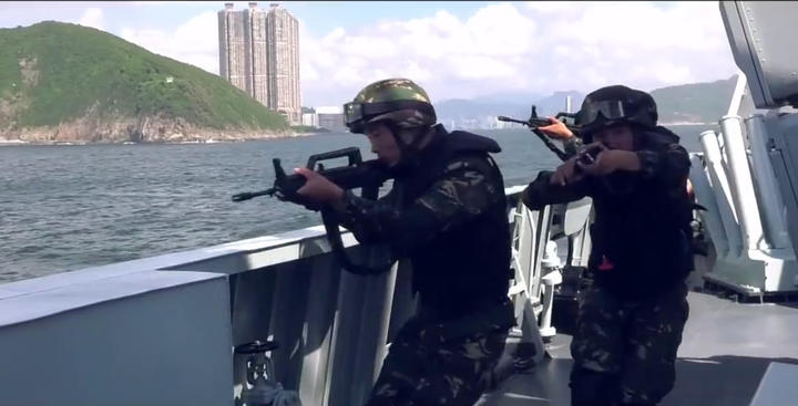 This screengrab taken from undated handout three-minute promotional video received on August 1, 2019 from China's People's Liberation Army (PLA) Hong Kong Garrison shows armed PLA soldiers on a boat during a drill in Hong Kong waters.