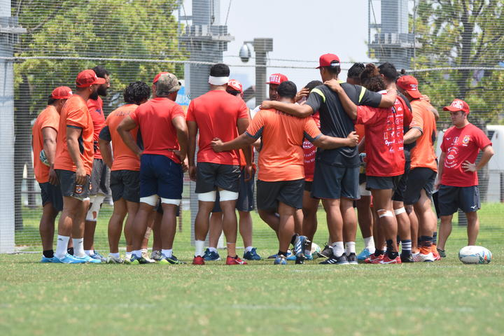 The 'Ikale Tahi players huddle together during training in Japan.