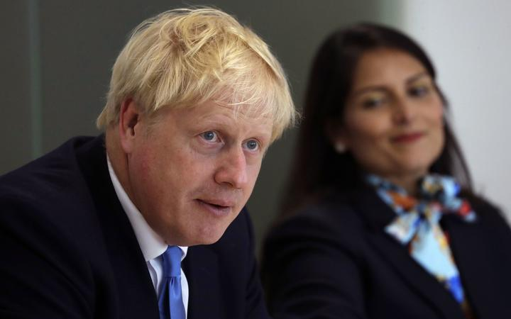 Britain's Prime Minister Boris Johnson (L), accompanied by Britain's Home Secretary Priti Patel, speaks at the first meeting of the National Policing Board at the Home Office in London, on July 31, 2019. (Photo by Kirsty Wigglesworth / POOL / AFP)
