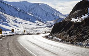 Road winding through a snow covered Lewis Pass, Canterbury, South Island, New Zealand