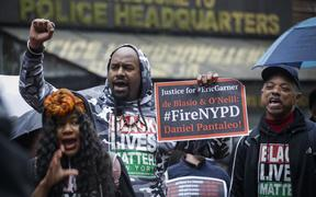 (FILES) In this file photo taken on May 13, 2019 People protest outside the police headquarters while a disciplinary hearing takes place for officer Daniel Pantaleo in New York City.