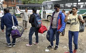 Tourists wait for buses to leave Kashmir in Srinagar on August 3, 2019.