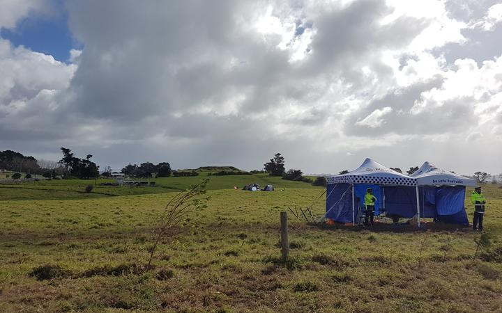 Police officers standing at the previous frontline, with occupiers who moved their tents camping further on in Ihumātao