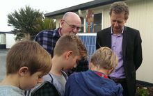 Russel Norman and Laingholm Primary School students looking at solar equipment.