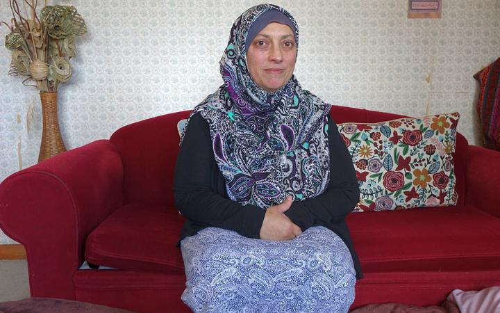 Woman in paisley pattern hijab sits on a red couch
