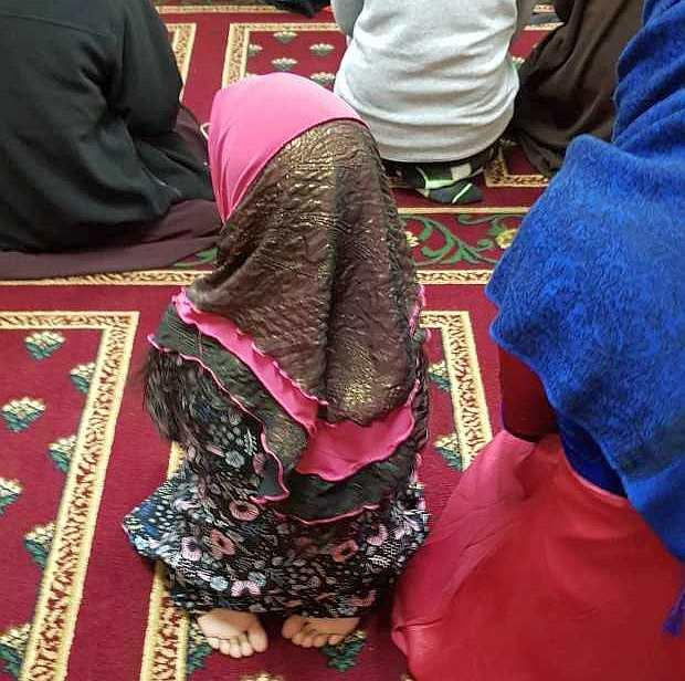 Small child in pink and black hijab