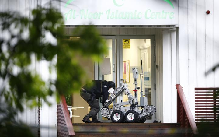 A Norwegian police expert manipulates a robot in front of the Al-Noor Islamic Centre where a gunman opened fire, injuring one person.