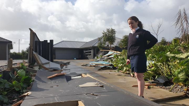 New Plymouth Girls High student is 17 year old Ciara Parkes stands in the debris  of a fence blown over.