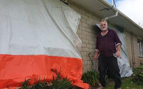 John Bamford outside his New Plymouth home that was damaged by the storm, which also injured his wife.