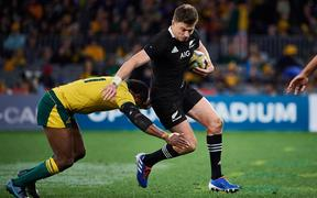 All Blacks first-five/fullback Beauden Barrett tries to evade a tackle by Australian winger Marika Koroibete.
